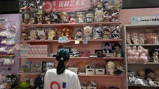 Une vendeuse devant un rayon de poupées inspirées d'émissions de téléréalité, à Pékin, en Chine, le 2 septembre 2021. (JADE GAO / AFP)