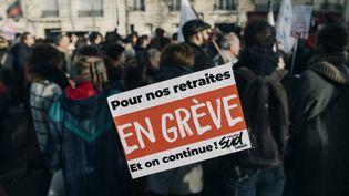 Un autocollant sur la vitre d'un bus devant la manifestation contre la réforme des retraites, à Paris, le 10 décembre 2019. (MATHIAS ZWICK / HANS LUCAS / AFP)