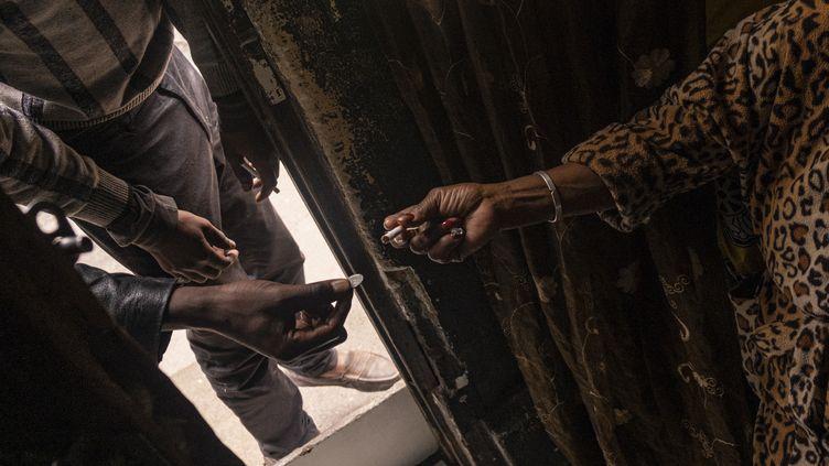 Un homme achèteune cigarette à une vendeuse à la sauvette quelque part en Afrique du Sud le 9 avril 2020, pendant le confinement lié au coronavirus. Les autorités ont interdit la vente de cigarettes pendant cette période de confinement. (EMMANUEL CROSET / AFP)