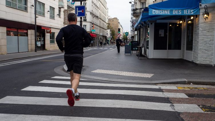 Un homme court dans les rues de Paris, le 8 novembre 2020. (RICCARDO MILANI / HANS LUCAS / AFP)