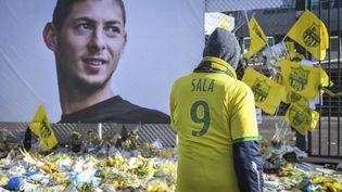 Des supporters rendent hommage à l'attaquant argentin Emiliano Sala, devant son portrait,au stade de la Beaujoire à Nantes, le 10 février 2019. (LOIC VENANCE / AFP)