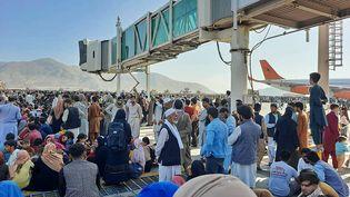 Une foule patiente sur le tarmac de l'aéroport de Kaboul (Afghanistan), dans l'espoir de réussir à quitter le pays, après l'entrée des talibans dans la ville. (AFP)