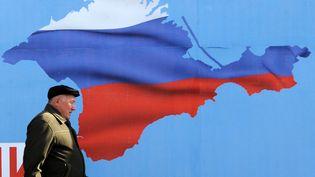 Un homme passe devant une affiche représentant le territoire de la Crimée aux couleurs de la Russie, à Sébastopol (Ukraine), le 11 mars 2014. (VIKTOR DRACHEV / AFP)