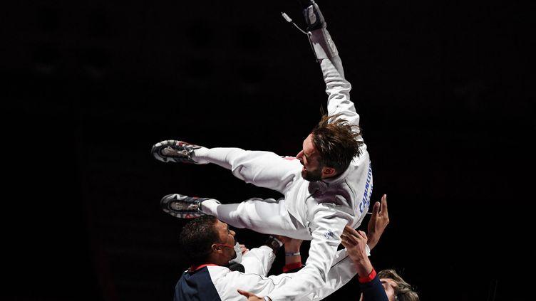 Romain Cannone porté en triomphe par les membres de l'équipe de France après son titre de champion olympiqué à l'épée, le 25 juillet 2021 à Tokyo. (MOHD RASFAN / AFP)
