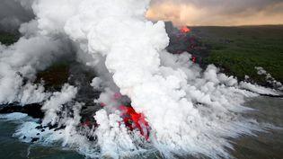 De la lave du Piton de la Fournaise se jette dans l'océan, à La Réunion, le 5 avril 2007. (RICHARD BOUHET / AFP)