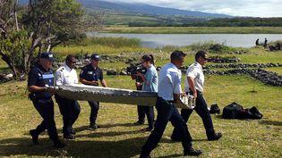 Les forces de l'ordre évacuentle fragment d'aile d'avion découvert le 29 juillet 2015 à La Réunion. (YANNICK PITOU / AFP)