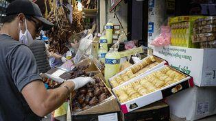 Un vendeur prépare une boîte de dattes à l'extérieur d'une épicerie dans le 18e arrondissement de Paris, le 24 avril 2020, au premier jour du ramadan. (GEOFFROY VAN DER HASSELT / AFP)