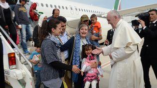 Le pape François accueille une famille de réfugiés syriens venantde Lesbos (Grèce) à la sortiede son avion, le 16 avril 2016 à l'aéroport de Ciampino à Rome (Italie). (FILIPPO MONTEFORTE / AFP)