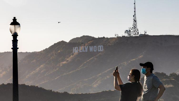 """Un couple prend un photo à l'observatoireGriffith, avec une vue sur le signe """"Hollywood"""" à Los Angeles (mai 2020). (APU GOMES / AFP)"""