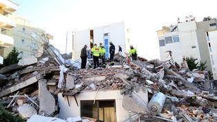Des sauveteurs s'affairent sur les décombres d'un immeuble détruit par un séisme, à Durrës (Albanie), le 26 novembre 2019. (GENT SHKULLAKU / AFP)