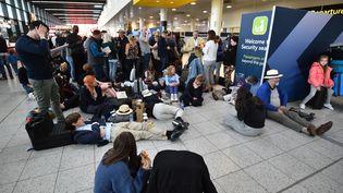 Des passagers attendent dans le terminal Nord de l'aéroport de Gatwick, près de Londres (Royaume-Uni) alors que les vols sont suspendus, le 20 décembre 2018. (GLYN KIRK / AFP)