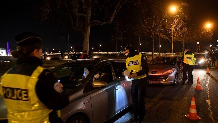 Des policiers vérifient les autorisations de déplacement des conducteurs à Paris, lors du couvre-feu, le 15 décembre 2020. (ALAIN JOCARD / AFP)