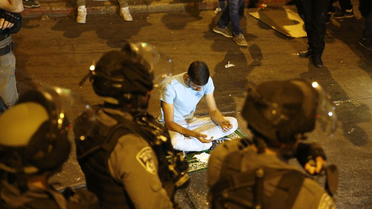 Les forces de sécurité israéliennes encadrent des prières de nuit, organisées en signe de protestation par les musulmans palestiniens devant l'entrée principale de la mosquée Al-Aqsa à Jérusalem, le 23 juillet 2017. (AHMAD GHARABLI / AFP)