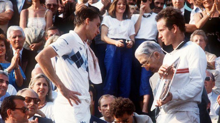 Ivan Lendl attend de soulever la Coupe des Mousquetaires à côté de John McEnroe (1984) (DOMINIQUE FAGET / AFP)