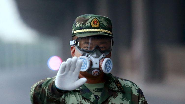 Un policier muni d'un masque bloque une rue menant au site des explosions, le 17 août 2015, à Tianjin. (KIM KYUNG HOON / REUTERS)