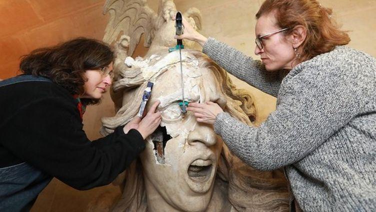 """Des restauratrices travaillent sur lesœuvres abîmées à l'Arc de triomphe, lors d'une journée de mobilisation des """"gilets jaunes"""". (MAXPPP)"""