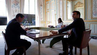 Le président Emmanuel Macron lors de sa discussion avec les dirigeants du G20 sur le coronavirus à l'Elysée le 26 mars 2020. (BENOIT TESSIER / AFP)