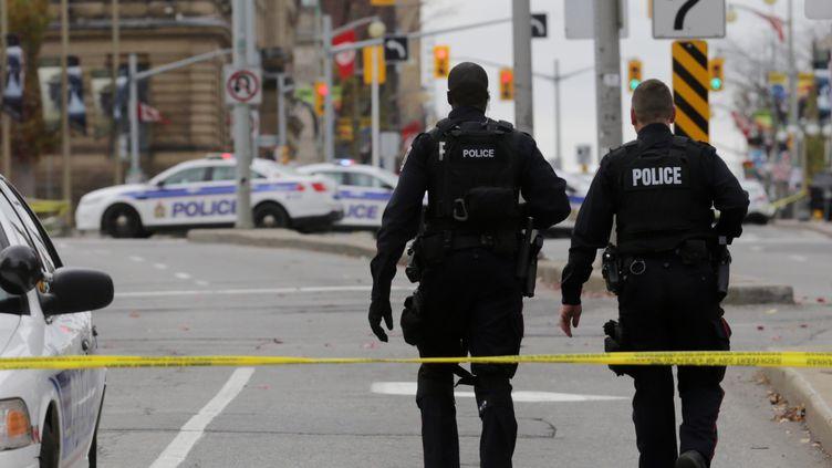 Des policiers marchent dans une rue d'Ottawa après une fusillade au Parlement canadien, le 22 octobre 2014. (MIKE CARROCCETTO / GETTY IMAGES / AFP)