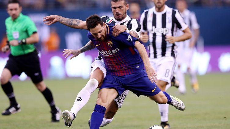 Le Barcelonais Lionel Messi à la lutte avec le défenseur turinois Stefano Sturaro. (ELSA / GETTY IMAGES NORTH AMERICA)