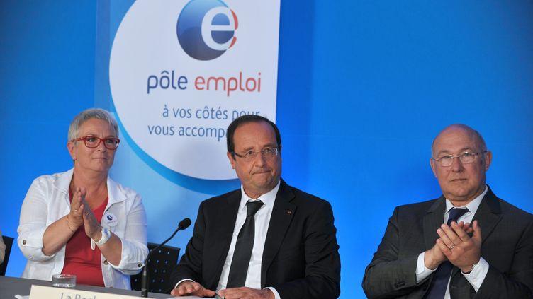François Hollande, entouré de Michel Sapin, le ministre du Travail, et de Catherine Derre, directrice d'une agence Pôle emploi, à La Roche-sur-Yon (Vendée), le 6 août 2013. (FRANK PERRY / AFP)