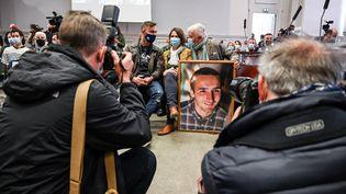 Les parents d'Arthur Noyer et son frère ont amené avec eux le portrait du jeune caporal, lors du premier jour du procès de Nordahl Lelandais, à Chambéry (Savoie), le 3 mai 2021. (PHILIPPE DESMAZES / AFP)