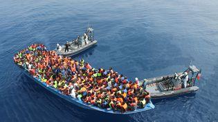 Des migrants sont secourus par des bateaux mis à disposition par l'armée irlandaise, en pleine Méditerranée, le 6 juin 2015. (VAN SEKRETAREV / AP / SIPA)