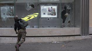 Un manifestant lance des pavés sur la vitrine de l'agence bancaire LCL, à Paris le 8 décembre 2018. (ANTONI LALLICAN / HANS LUCAS / AFP)