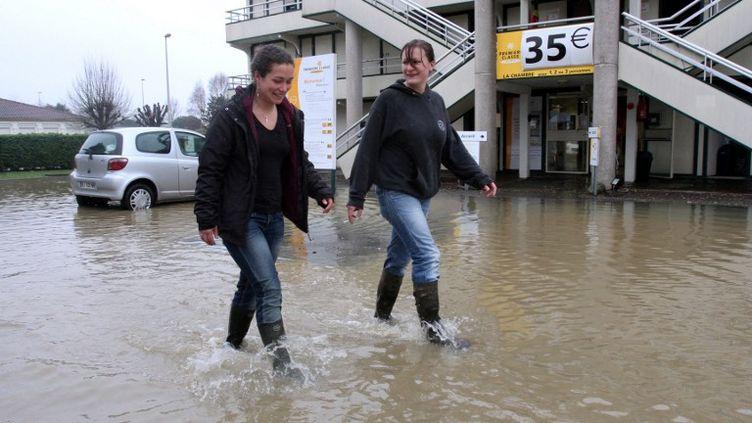 Deux jeunes femmes marchent dans une rue inondée de Tarbes (Hautes-Pyrénées), le 25 janvier 2014. ( AFP )