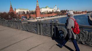 Une passante masquée traverse un pont près du Kremlin, le 26 mars 2020 à Moscou (Russie). (YURI KADOBNOV / AFP)