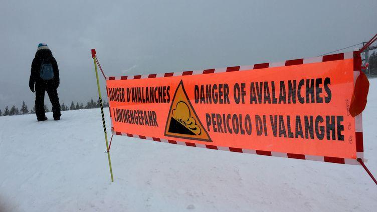 Une banderole met en garde contre le risque d'avalanche le 13 février 2016 auxCarroz d'Araches en Haute-Savoie. (DENIS CHARLET / AFP)