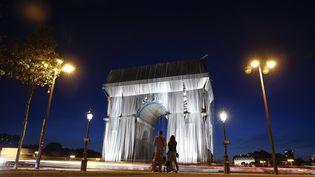 Un couple contemple l'oeuvre posthume de Christo, l'Arc de Triomphe empaqueté, le 12 septembre au soir. Le monument est alorspartiellementrecouvert de tissu argenté bleuté maisl'oeuvre n'est pas achevée. (YOAN VALAT / MAXPPP)