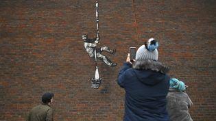 Graffiti du street artist britannique Banksy peint le 4 mars 2020 sur le mur de la prison de Reading, où fut incarcéré Oscar Wilde, de 1895 à 1897, pour homosexualité. (BEN STANSALL / AFP)