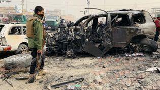 Des personnes à proximité d'une carcasse de voiture calcinée, le 20 décembre 2020, à Kaboul, en Afghanistan. (HAROON SABAWOON / ANADOLU AGENCY / AFP)