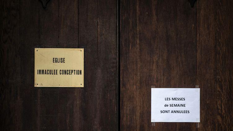 Un écriteau annonce l'annulation des messes sur la porte d'entrée de l'église de l'Immaculée Conception de Lyon, le 15 mars 2016. (JEFF PACHOUD / AFP)