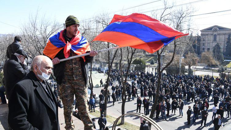 Un homme brandit un drapeau arménien pendant une manifestation pour demander la démission du Premier ministre, Nikol Pachinian, à Erevan, vendredi 26 février 2021. (ILIYA PITALEV / SPUTNIK / AFP)