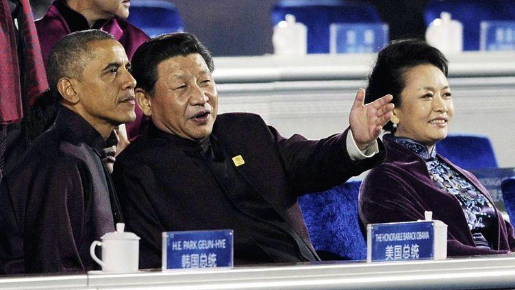 Les présidents américain, Barack Obama, et chinois, Xi Jinping, au côté de son épouse Peng Liyuan, lors du sommet pour la coopération économique en Asie-Pacifique (Apec), le 10 novembre 2014 à Pékin (Chine). (MISTURU TAMURA / YOMIURI / AFP)