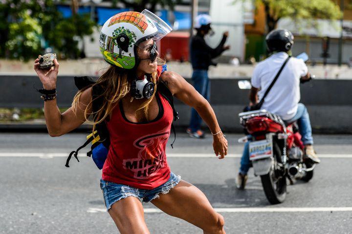 Caterina Ciarcelluti lançant le 1er mai 2017, une poignée de pierres vers les militaires à Caracas (Venezuela). (FEDERICO PARRA / AFP)