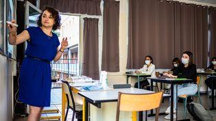 Une enseignante donne cours au lycée Arago de Perpignan (Pyrénées-Orientales) le 10 juin 2020 à des élèves masqués alors que l'épidémie de coronavirus recule en France. (JEAN-CHRISTOPHE MILHET / HANS LUCAS / AFP)