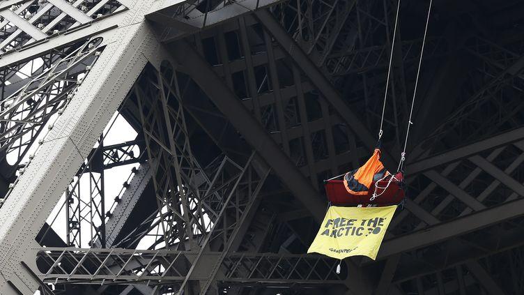 """Perché sur une nacelle, le militant de greepeace avait déployé, samedi 26 octobre, une banderole sur laquelle on pouvait lire """"Free the Artic 30"""" (Libérez les 30 de l'Arctique) et """"Militants en prison, climat en danger"""". (THOMAS SAMSON / AFP)"""