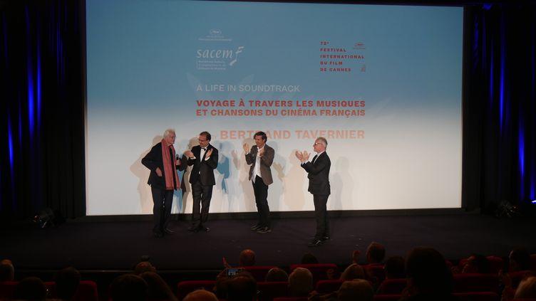 Bertrand Tavernier est applaudi par, Jean-Noël Tronc, directeur général de la Sacem, Stéphane Lerouge, Thierry Frémaux, délégué général du Festtival de Cannes. (Lorenzo Ciavarini Azzi/franceinfo Culture)
