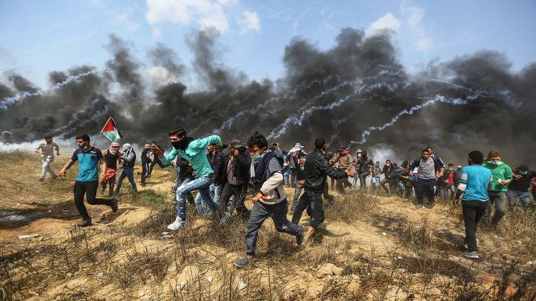 Des manifestants palestiniens fuient les gaz lacrymogènes de l'armée israélienne, le 27 avril 2018 à Gaza. (MUSTAFA HASSONA / ANADOLU AGENCY / AFP)