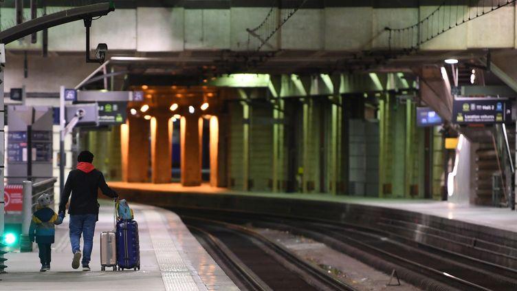 Un passager accompagné d'un enfant, gare Montparnasse à Paris, le 11 décembre 2019. (ALAIN JOCARD / AFP)