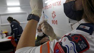 Une soignante prépare une dose de vaccin contre le Covid-19, le 18 février 2021 à Tel Aviv, en Israël. (GIL COHEN-MAGEN / AFP)