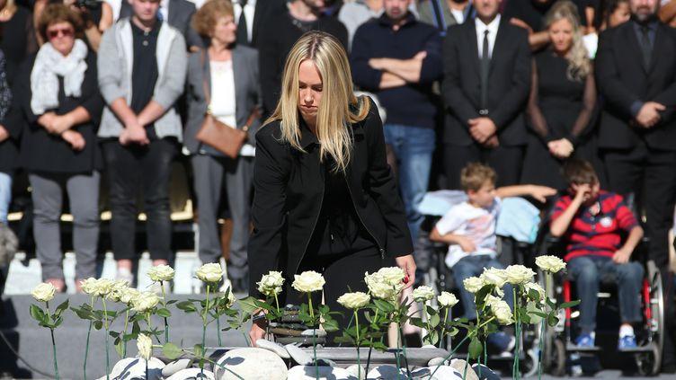 Une femme dépose une rose blanche représentant l'une des 86 victimes de l'attentat de Nice, le 15 octobre 2016. (ERIC GAILLARD / AFP)