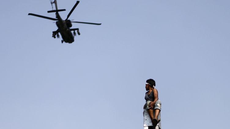 Un manifestant observe un hélicoptère de l'armée égyptienne, le 2 juillet 2013, au Caire. Les Etats-Unis ont annoncé le 9 octobre 2013 qu'ils ne livreront plus d'hélicoptères Apache à l'Egypte. (MAHMUD KHALED / AFP)