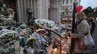 Une femme dépose des fleurs en hommage aux victimes de l'attentat commis à la basilique Notre-Dame de l'Assomption, à Nice, le 31 ocotbre 2020. (VALERY HACHE / AFP)