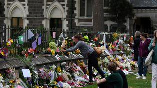 Des passants déposent des fleurs sur les lieux de l'attaque d'une mosquée àChristchurch (Nouvelle-Zélande), le 16 mars 2019. (ANTHONY WALLACE / AFP)