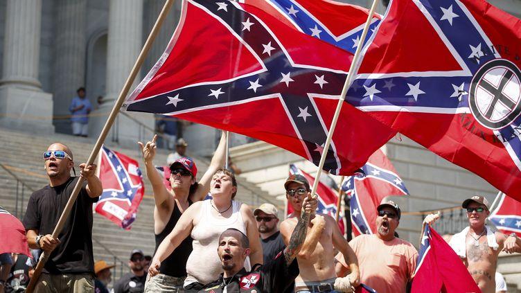 Des membres du Ku Klux Klan brandissent le drapeau confédéré devant le parlement de Caroline du Sud, à Columbia, le 18 juillet 2015. (CHRIS KEANE / REUTERS)