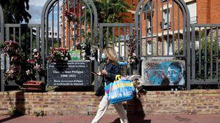 Une femme passe, le 30 août 2020, devant les plaques commémoratives sur le boulevard de Montrouge (Hauts-de-Seine) où Clarissa Jean-Philippe a été assassinée le 8 janvier 2015. (THOMAS COEX / AFP)