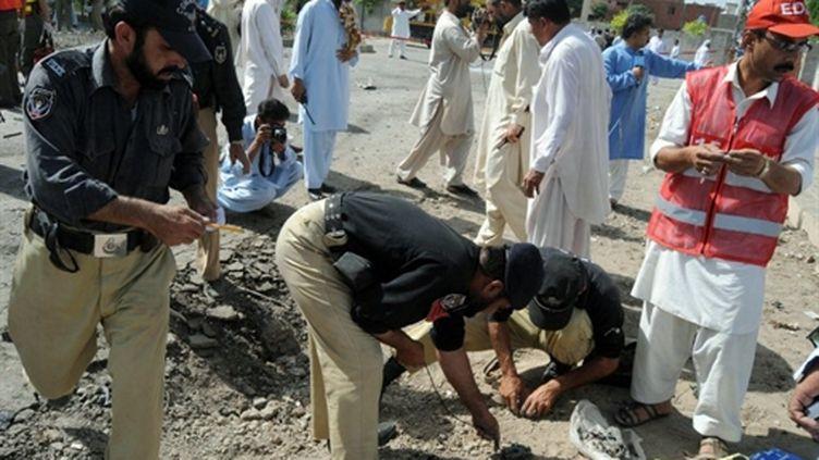 La police pakistanaise cherche des indices après l'attentat à la bombe, le 20 mai 2011. (AFP - A. Majeed)